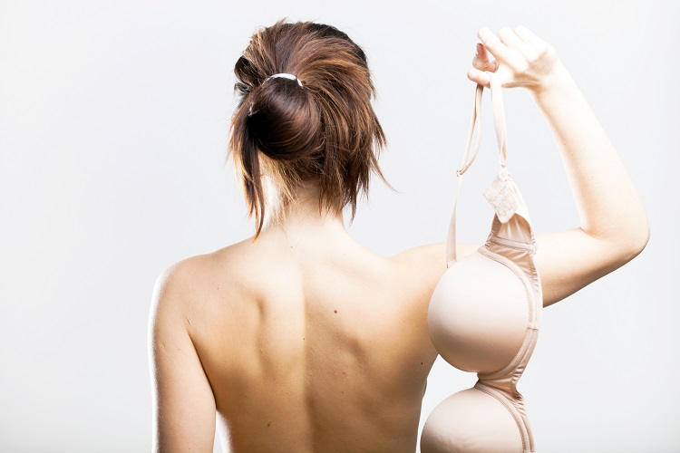 Naked woman back view holding bra in her hand
