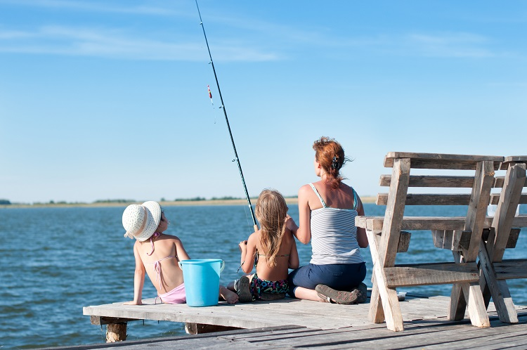 Mother and her two daughters fishing off an old wooden pier